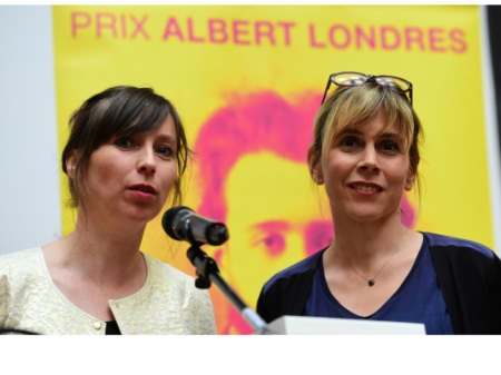 French journalists Cecile Allegra (R) and Delphine Deloget, winners of the Albert Londres prize in the audiovisual category, react after being awarded the 2015 Albert Londres prizes, the highest French-reporting journalism award, during a ceremony in Brussels, on May 30, 2015. AFP PHOTO / EMMANUEL DUNAND
